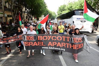 FILE PHOTO: Protestors march behind a banner of the BDS organization in Marseille, southern France, on June 13, 2015