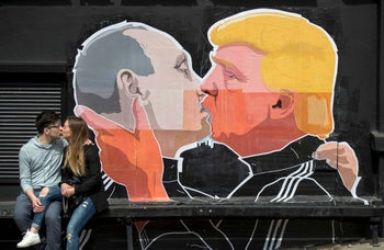 A couple kissing in front of graffiti depicting Russian President Vladimir Putin and U.S President Donald Trump kissing, in Vilnius, Lithuania.