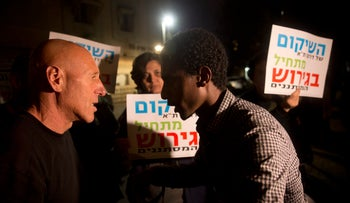 """Demonstrators for and against expulsion of asylum seekers at a Tel Aviv protest, January 9, 2018. The sign says: """"The rehabilitation of south Tel Aviv begins with the expulsion of the infiltrators."""""""