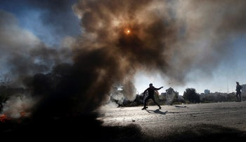 A Palestinian protester uses a slingshot at Israeli troops during clashes after U.S. President Donald Trump's recognition of Jerusalem as Israel's capital, near the West Bank city of Ramallah. December 8, 2017