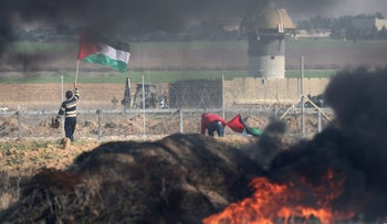 A demonstrator holds a Palestinian flag during clashes with Israeli troops near the border with Israel in the southern Gaza Strip January 9, 2018.