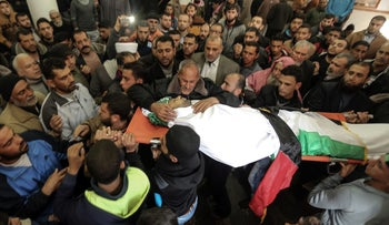 Mourners carry the body of Abdullah Zeidan, a 33-year-old fisherman, during his funeral in Gaza City on January 13, 2018.