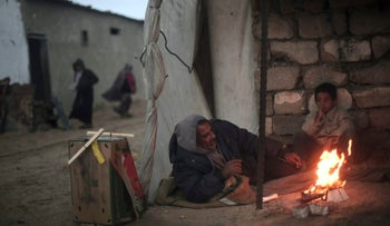 A Palestinian man and his son warm themselves by a fire during cold, rainy weather in a slum on the outskirts of the Khan Younis refugee camp, southern Gaza Strip, Friday, Jan. 5, 2018. (AP Photo/ Khalil Hamra)