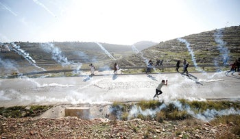 Palestinian demonstrators run as tear gas is fired by Israeli troops during clashes in the West Bank village of Nabi Saleh, near Ramallah January 13, 2018.