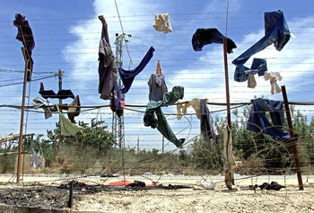 Clothes left behind by South Lebanon Army soldiers during the Israeli withdrawal are strewn on the barbed wire border fence between Israel and Lebanon as seen from Kfar Kila, 27 May 2000.