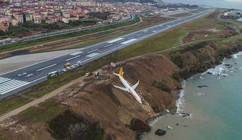 A Pegasus Airlines Boing 737 passenger plane is seen struck in mud on an embankment, a day after skidding off the airstrip, after landing at Trabzon's airport on the Black Sea coast on January 14, 2018
