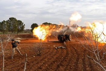 An opposition fighter fires a gun from a village near al-Tamanah during ongoing battles with government forces in Syria's Idlib province on January 11, 2018.