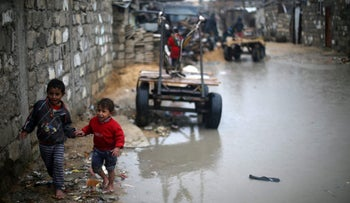 Palestinian children walk in a street on a rainy day in Khan Younis in the southern Gaza Strip January 6, 2018.