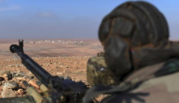 A member of the Syrian government forces looks out towards the horizon near Jabal al-Hass in the southern part of Aleppo province as they advance towards the Abu Duhur military airport in the ongoing offensive against opposition fighters on January 14, 2018