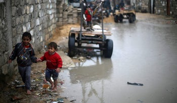 Palestinian children walk in a street on a rainy day in the Southern Gaza Strip on January 6, 2018.