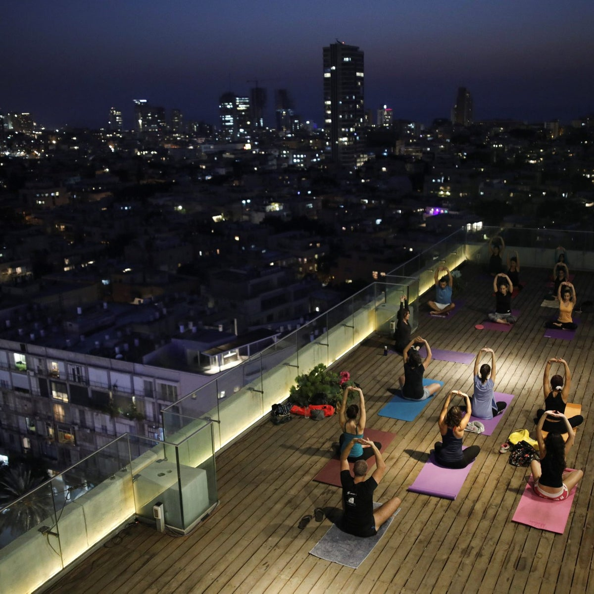 People participate in a yoga class on the rooftop of Tel Aviv municipality building, Tel Aviv, Israel, October 19, 2017.