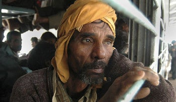 A migrant laborer from Bihar looks out from a train as he flees the northeastern Indian state of Assam, at the railway station in Gauhati, India, Tuesday, Jan. 9, 2007