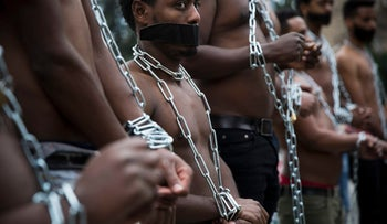 Eritrean migrants wear chains to mimic slaves at a demonstration against the Israeli government's policy outside the Knesset, in Jerusalem, Wednesday, Jan. 17, 2018.