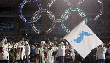 In this Feb. 10, 2006, file photo, Korea flag-bearer's Bora Lee and Jong-In Lee, carrying a unification flag lead their teams into the stadium during the 2006 Winter Olympics opening ceremony in Turin, Italy