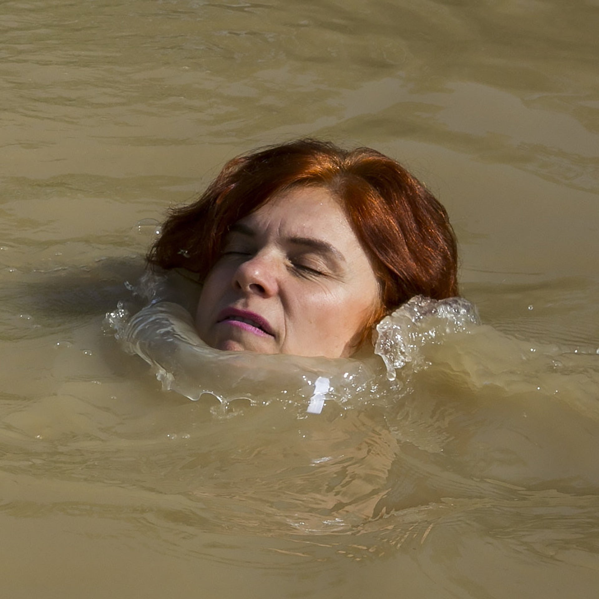 A visitor is baptizing in the Jordan river at Qasr el-Yahud. Safer in the water than on the ground.