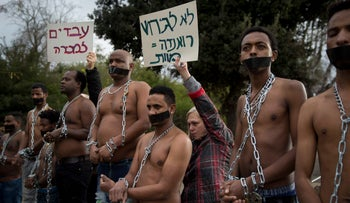 Eritrean asylum seekers wear chains to symbolize the slave trade at a demonstration against the Israeli government's intentions to forcibly deport them to Uganda and Rwanda outside the Knesset in Jerusalem on January 17, 2018.