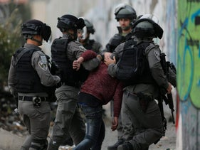 Israeli border police arrest a Palestinian in the West Bank, December 22, 2017