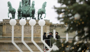 Rabbi inspect with a construction worker a giant Hanukkah Menorah, set up by the Jewish Chabad Educational Center, at the Pariser Platz in Berlin, Tuesday, Dec. 12, 2017. (AP Photo/Markus Schreiber)