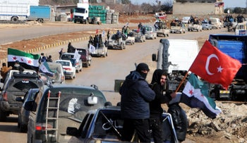 Turkey-backed fighters tour the Syrian town of Azes near the border of the two countries on January 19, 2018.