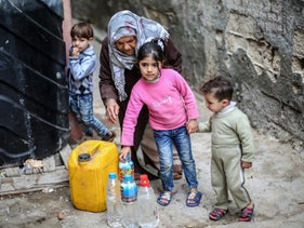 Palestinians filling bottles and jerricans with drinking water at the Al-Shati refugee camp in the southern Gaza Strip, March 22, 2017.