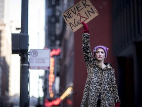 "A demonstrator holds a ""Never Again"" sign during the second annual Women's March Chicago in Chicago, Illinois, U.S. Jan. 20, 2018"