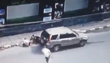 A car is seen plowing into a motorcycle in security footage of the incident that claimed an Israeli criminal's life in Thailand.
