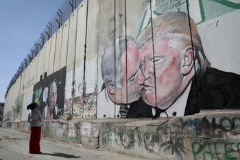 A woman looking at a mural depicting U.S. President Donald Trump and Prime Minister Benjamin Netanyahu kissing, on the West Bank separation barrier in Bethlehem, October 29, 2017.