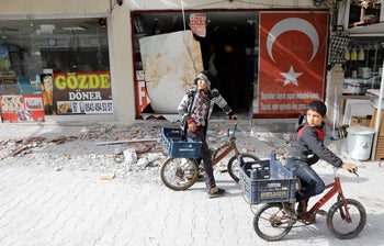 Boys standing in front of a building that was hit by rockets fired from Syria, in the border town of Reyhanli, Turkey, January 22, 2018.