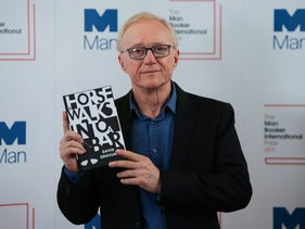 """Israeli author David Grossman posing with his book """"A Horse Walks Into a Bar"""" in London, June 13, 2017."""