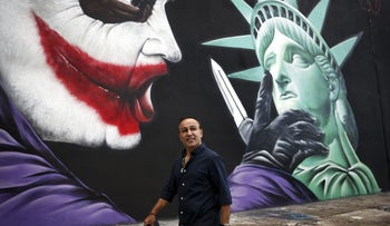Moishe Mana walking past a mural he commissioned.