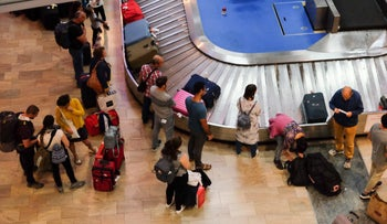 Passengers at Israel's Ben-Gurion International Airport wait to collect their luggage.