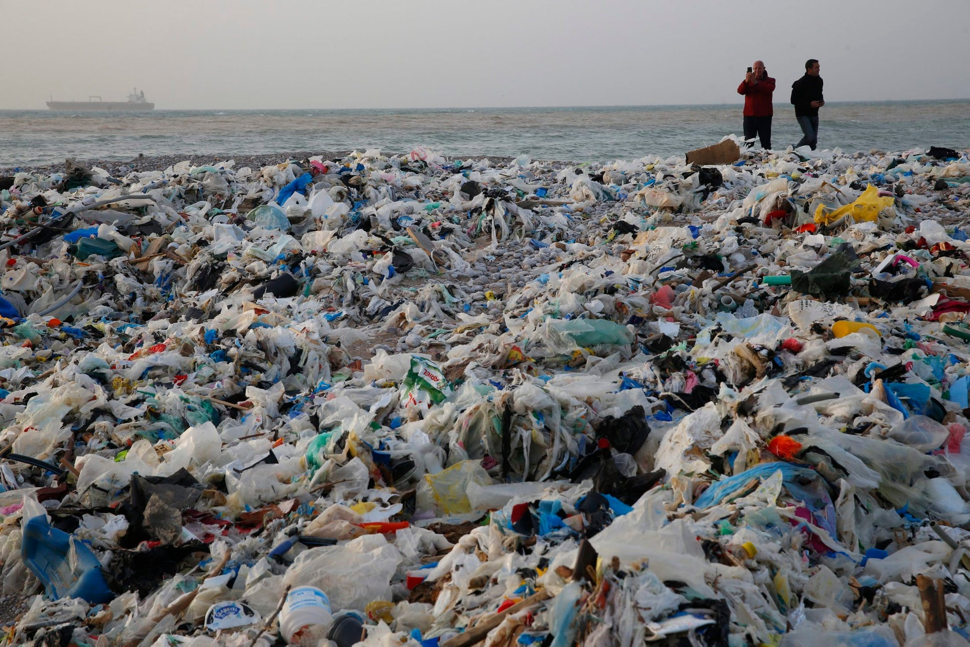 In this Monday, Jan. 22, 2018, photo, a man takes photos of piles of garbage washed on shore after an extended storm battered the Mediterranean country at Zouq Mosbeh costal town, north of Beirut, Lebanon. Environmentalists say a winter storm has pushed a wave of trash onto the Lebanese shore outside Beirut, stirring outrage over a waste management crisis that has choked the country since 2015.