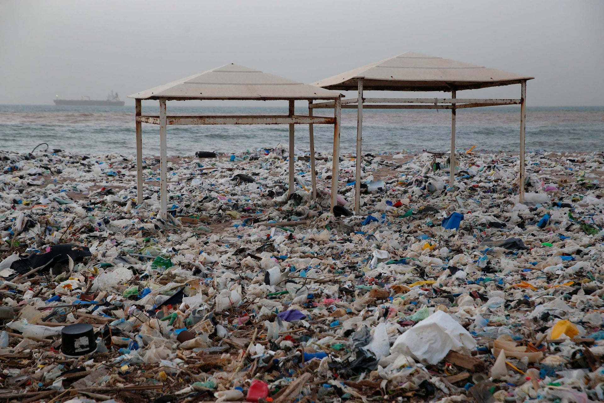 In this Monday Jan. 22, 2018, photo, two tents sit in piles of garbage covering the shore days after an extended storm battered the Mediterranean country at the Zouq Mosbeh costal town north of Beirut, Lebanon. Environmentalists say a winter storm has pushed a wave of trash onto the Lebanese shore outside Beirut, stirring outrage over a waste management crisis that has choked the country since 2015.