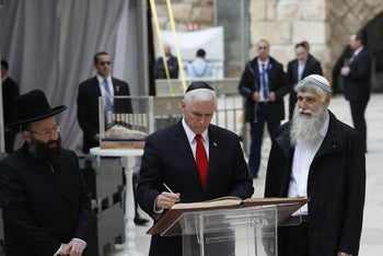 US Vice President Mike Pence (C) signs the guest book during a visit to Jerusalem's Western Wall on January 23, 2018.
