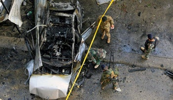 Lebanese army soldiers inspect a car that was destroyed in a bombing, in the southern port city of Sidon, Lebanon, Sunday, Jan 14, 2018.