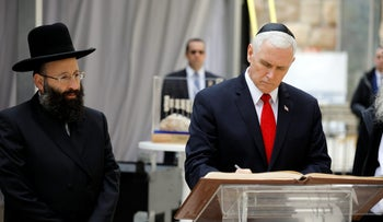 U.S. Vice President Mike Pence signs a guest book accompanied by the Rabbi of the Western Wall Shmuel Rabinovitch at the Western Wall in Jerusalem's Old City, January 23, 2018.