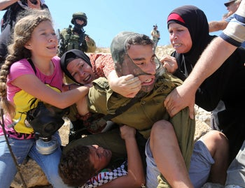 A photo showing Ahed Tamimi, left, fighting with other members of her family to free a boy held by an Israeli soldier during clashes in Nabi Saleh on August 28, 2015