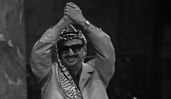 "Palestine Liberation Organization leader Yasser Arafat clasps his arms over his head as he addresses the United Nations General Assembly Nov. 13, 1974. ""I have come bearing an olive branch and a freedom fighter's gun,"" he said.  ""Do not let the olive branch fall from my hands."" (AP Photo/Marty Lederhandler)"