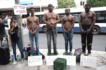 An image showing a mock slave auction staged in Tel Aviv as part of a protest against the Israeli government's decision to forcibly deport African asylum seekers.
