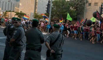 Police officers watch as participants in the gay pride parade march in Jerusalem, July 21, 2016.