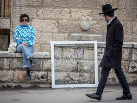 A Haredi man walks by a painting of a woman whose shirt reads 'open your eyes.' Next to it, sits artist Sara Erenthal.