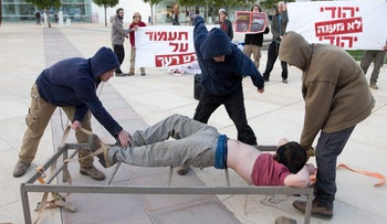 Right-wing activists reenact Shin Bet torture tactics during a demonstration in Tel Aviv, 2015.