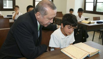 Turkish President Tayyip Erdogan looks on as a student reads the Koran at the Recep Tayyip Erdogan Imam Hatip School in Istanbul, Turkey, September 29, 2017. Picture taken September 29, 2017
