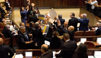Ushers scuffle with members of the Joint List who are holding signs in protest ahead of U.S. Vice President Mike Pence's address to the Knesset in Jerusalem January 22, 2018.