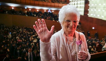 Holocaust survivor Liliana Segre waves at the end of a meeting with young students on the occasion of an Holocaust remembrance, at the Arcimboldi theatre in Milan, Italy, Wednesday, Jan. 24, 2018.