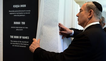 Prime Minister Benjamin Netanyahu looks at Book of Names listing details at the opening of the Permanent Exhibition SHOAH at former Nazi death camp in the Auschwitz-Birkenau State Museum, Block 27 in Oswiecim on June 13, 2013.