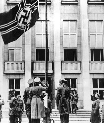 In this file photo taken in Sept. 1939, Nazi Germany, foreground left, and Soviet Red Army, foreground right, officers salute the Nazi swastika flag during their joint parade in Brest-Litovsk celebrating a border demarcation in Poland following  Hitler's invasion of Poland.
