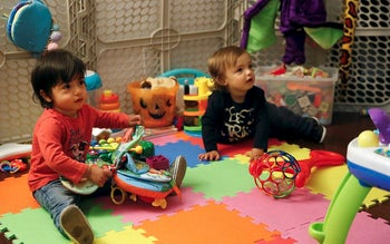 Sixteen-month-old Ethan Dvash-Banks, left, and his twin brother, Aiden, play in the living room of their apartment Tuesday, Jan. 23, 2018, in Los Angeles