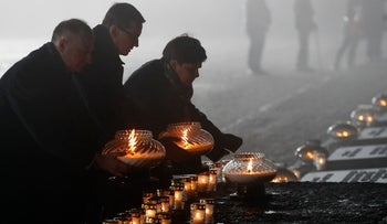 Polish Prime Minister Mateusz Morawiecki (center) places candles at the former Nazi German concentration and extermination camp Auschwitz-Birkenau, Poland, Saturday, January 27, 2018.
