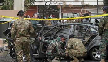 Lebanese army soldiers inspect a car that was destroyed in a bombing in Sidon, Jan 14, 2018